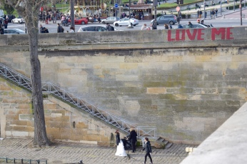 "Love the contrast of the ""Love Me"" graffiti with the wedding photos below"